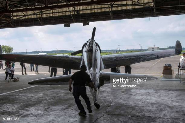 This picture taken on June 6 2017 shows a restored World War IIera Mitsubishi A6M Type 22 Zero fighter leaving a hangar at an airfield in Ryugasaki...