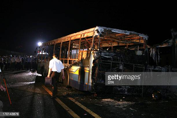 This picture taken on June 7 2013 shows investigators at the scene of a bus that caught fire on the BRT elevated road in the city of Xiamen China's...