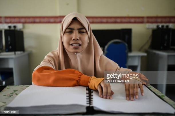 This picture taken on June 7 2017 shows a visually impaired Malaysian Islamic studies student reading and memorising the Quran from a Braille copy of...