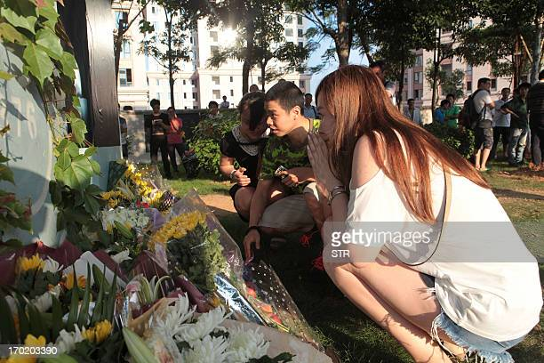 This picture taken on June 8 2013 shows people gathering to place flowers beneath the BRT elevated road where a commuter bus was engulfed in flames...