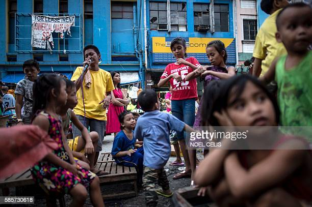 This picture taken on June 8 2016 shows children waiting their turn to sing karaoke along a street in the Divisoria market in Manila Since winning...