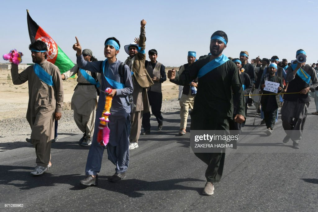 This picture taken on June 8, 2018 shows Afghan peace activists shouting slogans in demand to an end to the war as they start their march from Helmand to Kabul in Ghazni province. - Hobbled by blisters and stalked by hunger, dozens of Afghan protesters are marching hundreds of kilometres across the war-torn country demanding an end to the nearly 17-year conflict. (Photo by ZAKERIA HASHIMI / AFP) / To go with AFP story: AFGHANISTAN-UNREST-DEMONSTRATION, Focus by Zakeria Hashimi & Mamoon Durrani