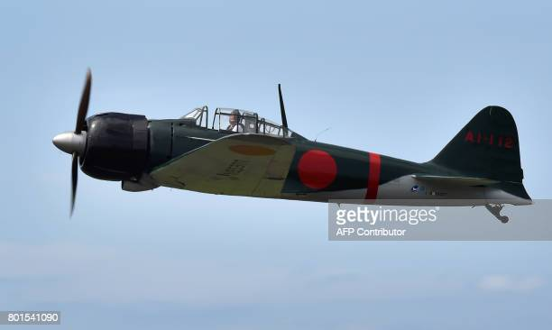 This picture taken on June 9 2017 shows a restored World War IIera Mitsubishi A6M Type 22 Zero fighter flying over an airfield in Ryugasaki Ibaraki...