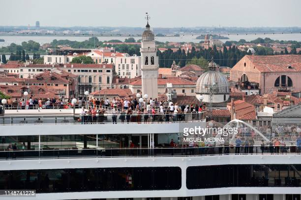 This picture taken on June 9 2019 shows people on board of the MSC Magnifica cruise ship arriving in the Venice Lagoon seen from San Maggiore's bell...