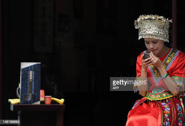 This picture taken on June 9 shows a Chinese ethnic minority tribeswoman waits for customers at a stall in Qingyanguzhen located in the southern...
