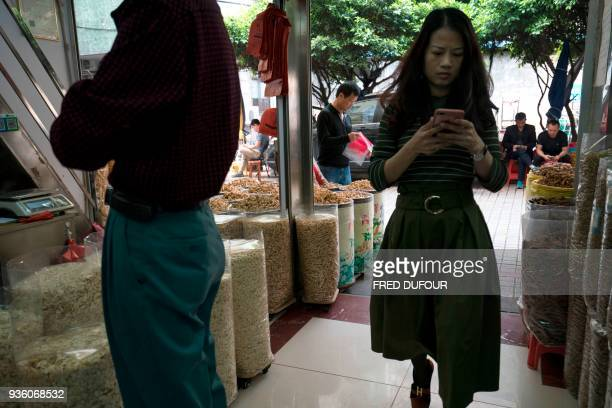 This picture taken on March 1 2018 shows a woman walking past a stall selling ingredients for traditional Chinese medicine at a popular market in...