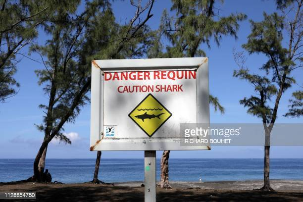This picture taken on March 1 2019 shows a sign warning on the danger of shark attacks at the L'EtangSale beach on the Indian Ocean island of La...