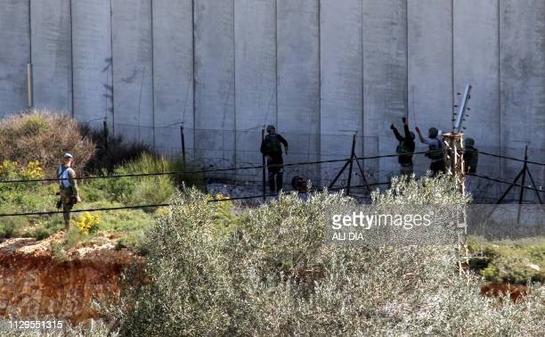 This picture taken on March 10 2019 from the southern Lebanese village of Kfar Kila shows Israeli soldiers taking down a barbed wire fence after...