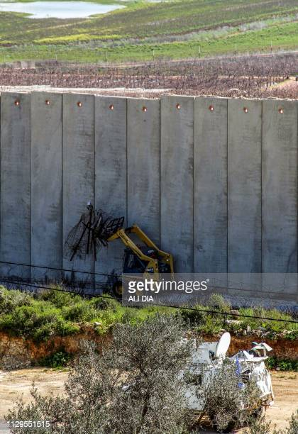 This picture taken on March 10 2019 from the southern Lebanese village of Kfar Kila shows an Israeli excavator removing the old barbed wire fence...
