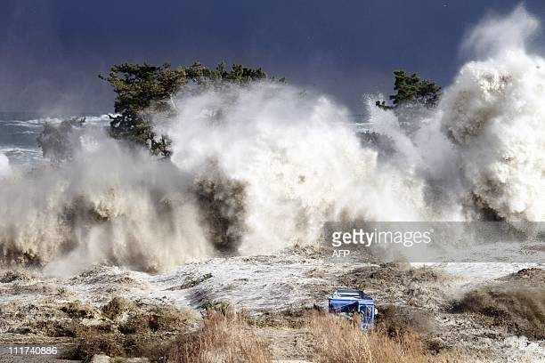 This picture taken on March 11 2011 by Sadatsugu Tomizawa and released via Jiji Press on March 21 2011 shows tsunami waves hitting the coast of...
