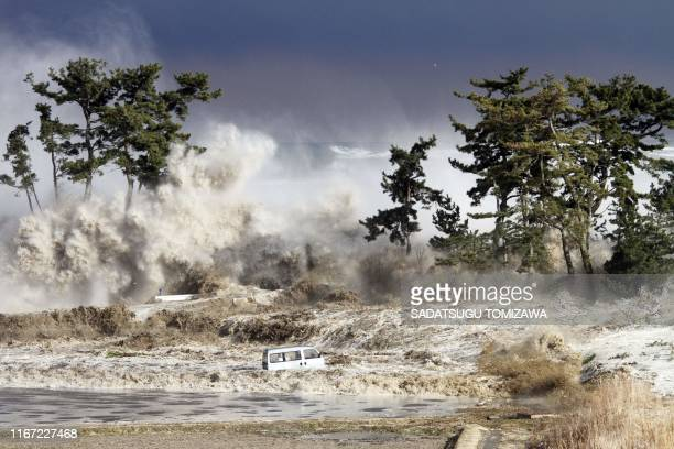 This picture taken on March 11, 2011 by Sadatsugu Tomizawa and released via Jiji Press on March 21, 2011 shows tsunami waves hitting the coast of...