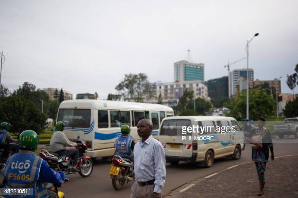 This picture taken on March 11 2014 shows pedestrians walking in a street of the Rwandan capital Kigali The Rwandan Development Board says that they...
