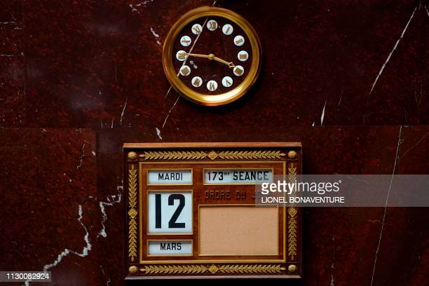 This picture taken on March 12 2019 shows a clock and the date of the 173rd session of questions to the French government at the National Assembly in...