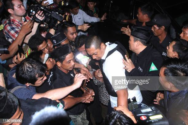 TOPSHOT This picture taken on March 12 2019 shows Indonesian police trying to shield Siti Aisyah who was on trial in Malaysia for assassinating Kim...