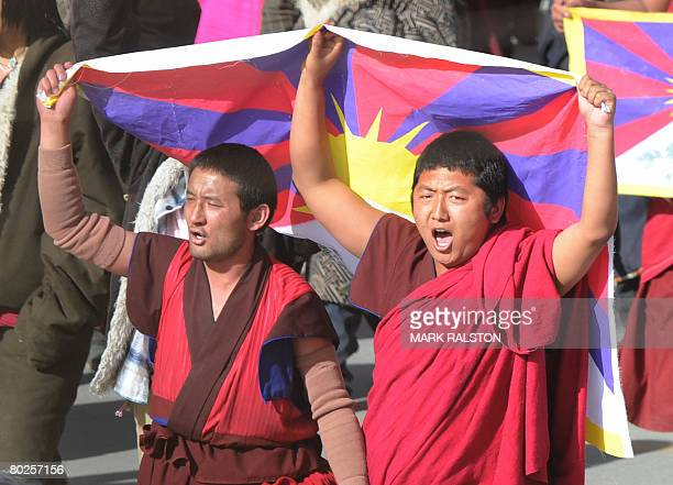 This picture taken on March 14, 2008 shows two Tibetan Buddhist monks shout slogans as they carry the Tibetan national flag during a protest near the...