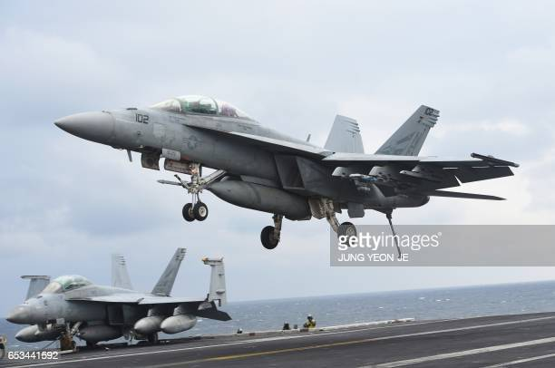 This picture taken on March 14 2017 shows a twoseater F/A18F Super Hornet landing on the deck of the Nimitzclass aircraft carrier USS Carl Vinson...