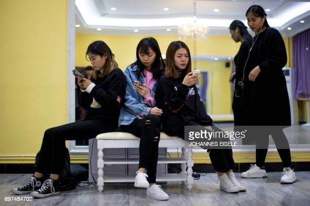 This picture taken on March 14, 2017 shows students looking at their smartphones during a class at the Yiwu Industrial & Commercial College in Yiwu,...