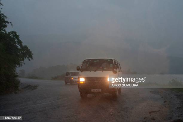 This picture taken on March 15, 2019 shows vehicules as rain, which is believed to be the beginning of Tropical cyclone Idai coming from central...