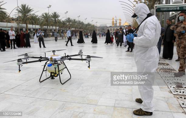 This picture taken on March 15, 2020 shows an unmanned aerial vehicle or drone being used by Iraqi health workers to disinfect the area around the...