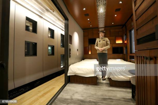 This picture taken on March 16 2017 shows a crew member introducing a suite room of the Train Suite ShikiShima operated by East Japan Railway in...