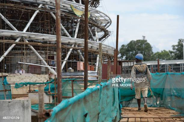 This picture taken on March 17 2014 shows a construction worker walking through the site of the Kigali Conference Centre currently being built in the...