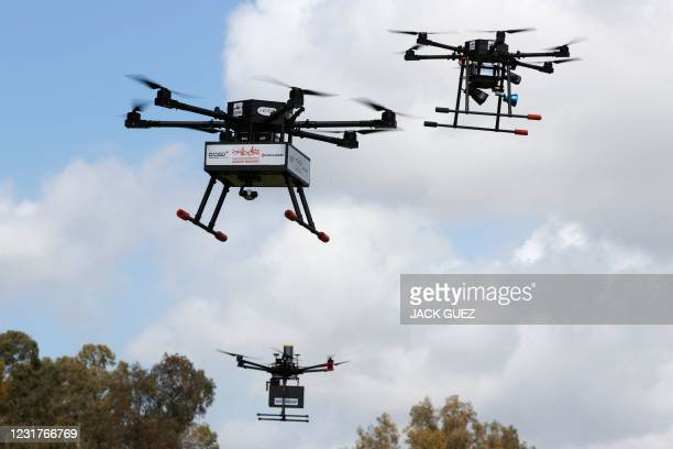 This picture taken on March 17, 2021 in the Israeli coastal city of Hadera shows an unmanned aerial vehicle carrying fast food deliveries as part of...