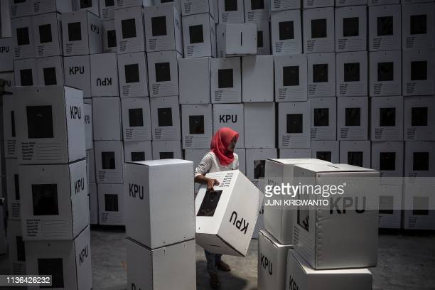 TOPSHOT This picture taken on March 18 2019 shows an Indonesian election commission worker arranging ballot boxes in Surabaya in preparation for the...