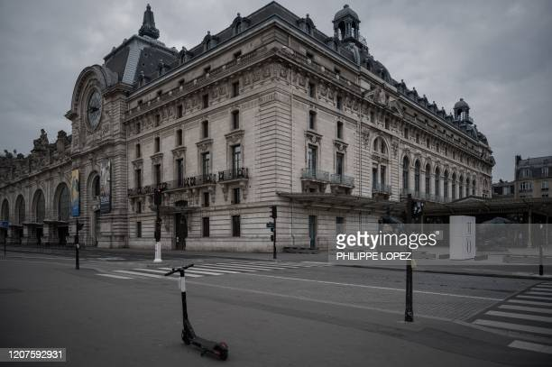 This picture taken on March 18, 2020 shows an electric scooter on the pavement in front of the closed Orsay museum, in Paris, as a strict lockdown...