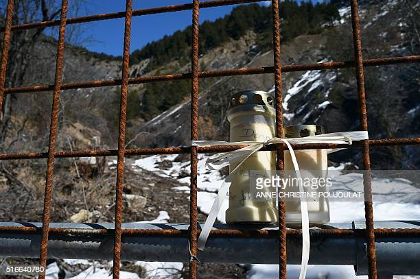 This picture taken on March 18 shows a candle tied to a fence by the sanctuarized Germanwings aircrash site in the mountains near Le Vernet southern...