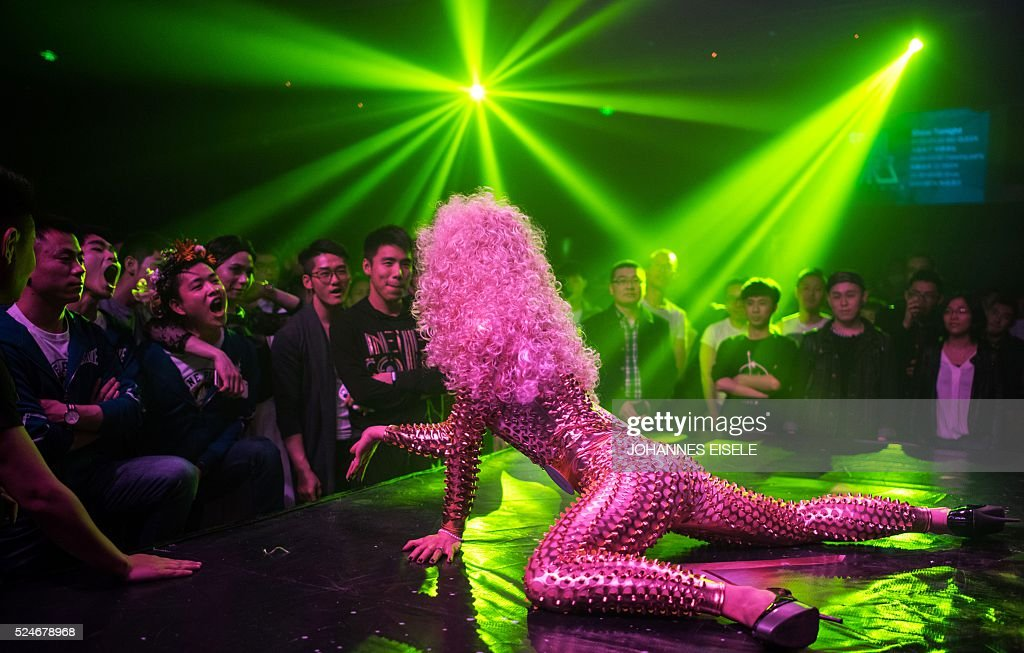 This picture taken on March 18, 2016, shows Yu Xiaoyang - who uses the stage name Xiao Bai meaning 'Little White' - performing during the semi-final of Big Queen, a cross-dressing contest in the Icon Club in Shanghai. In a bouffant blonde wig and outsize eyelashes, Yu Xiaoyang flamboyantly parades across a Shanghai stage, his fake breasts filling his skintight golden jumpsuit. Yu was among 20 contestants taking part in a cross-dressing competition in China's commercial hub. the contry only decriminalised homosexuality in 1997 and discrimination is common, although tolerance is greater in major cities, and the Shanghai Pride group mounts an annual series of events for the lesbian, gay, bisexual and transgender (LGBT) community and their supporters. / AFP / JOHANNES