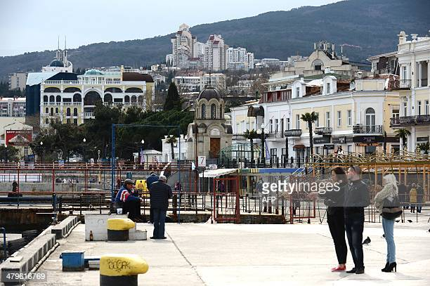 This picture taken on March 19 2014 shows people enjoying a walk in Yalta Crimea The new authorities of the Peninsula announced the nationalization...