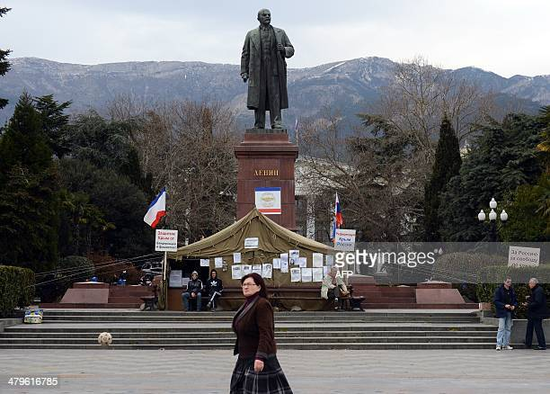 This picture taken on March 19 2014 shows people walking past a statue of Lenin in Yalta Crimea The new authorities of the Peninsula announced the...