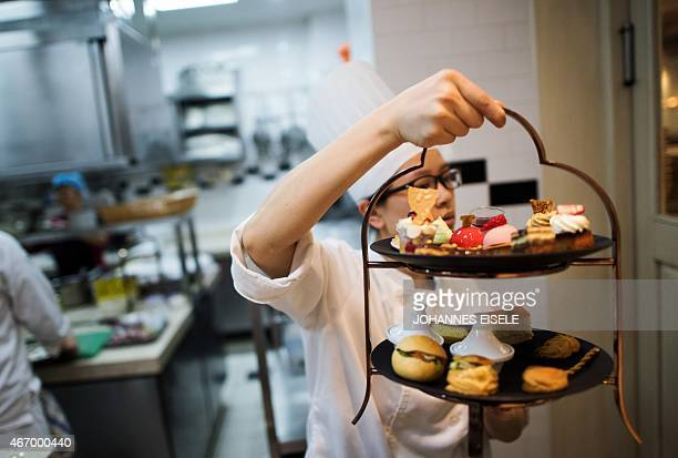 This picture taken on March 19 2015 shows a chef carrying desserts for the Goût de France event in the kitchen of the 'Paris Rouge' in Shanghai The...