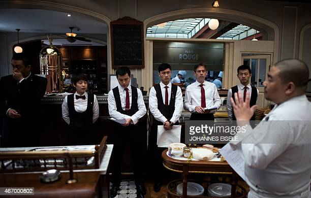This picture taken on March 19 2015 shows chef and owner of the Paris Rouge in Shanghai Stephane Liu explaining the menu to the waiters before the...