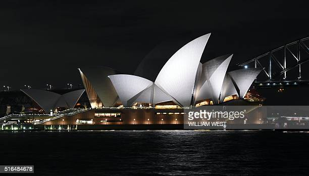 This picture taken on March 19 2016 shows the Sydney Opera House before the lights are turned off during the Earth Hour campaign in Sydney Millions...