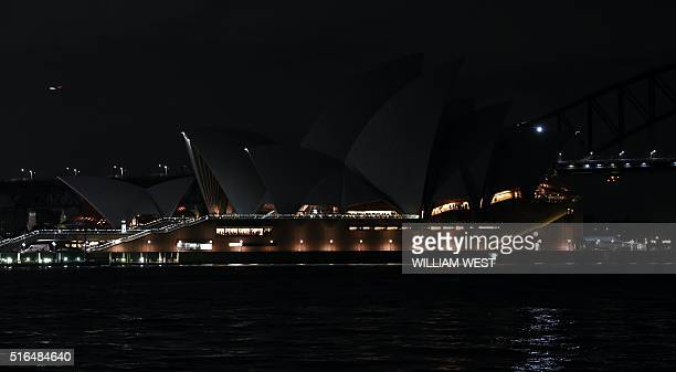 This picture taken on March 19 2016 shows the Sydney Opera House with the lights turned off during the Earth Hour campaign in Sydney Millions of...