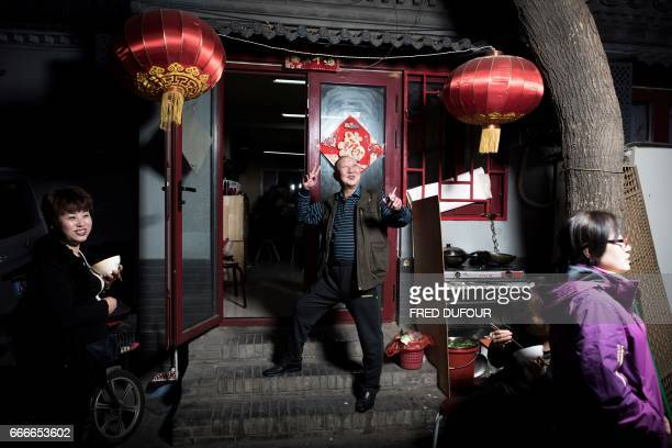 This picture taken on March 19 2017 shows a man posing with his clients in front of his restaurant in a hutong in Beijing With space scarce in the...