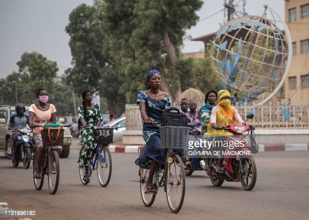 This picture taken on March 19, 2019 shows people riding bicycles and motorbikes around the United Nations roundabout in Ouagadougou.