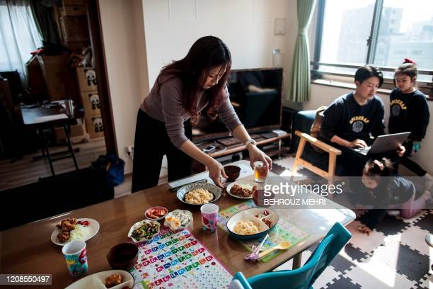 This picture taken on March 19, 2020 shows family of Yuki Sato , an employee in a start-up company, who works from home as a result of the COVID-19...