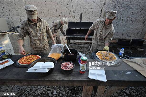 This picture taken on March 2 2011 shows US Marines of the 2nd Batallion 1st Marines Weapons Company cooking pizza in Laki Helmand province...