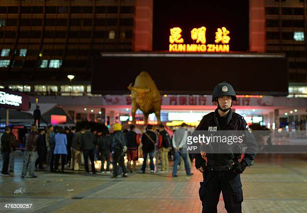 This picture taken on March 2 2014 shows a police stand guarding as Chinese mourners light candles at the scene of the terror attack at the main...