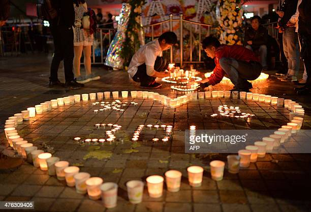 This picture taken on March 2 2014 shows Chinese mourners lighting candles at the scene of the terror attack at the main train station in Kunming...