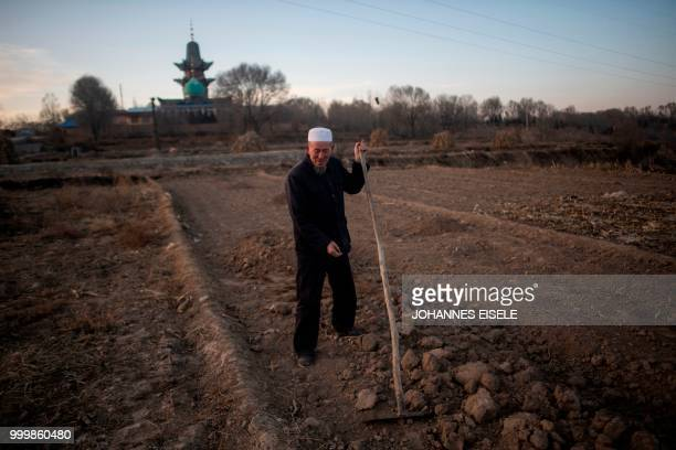 This picture taken on March 2 2018 shows an ethnic Hui Muslim man working in his field in front of a mosque in the suburbs of Linxia China's Gansu...