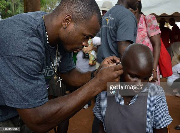 This picture taken on March 20 2011 shows Minnesota Vikings Running Back Adrian Peterson as he adjusts a Starkey hearing aid for a young girl in Gulu...