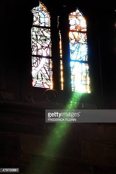 This picture taken on March 20 2014 shows a green ray optical phenomenon coming through a stainedglass window at the Strasbourg cathedral eastern...