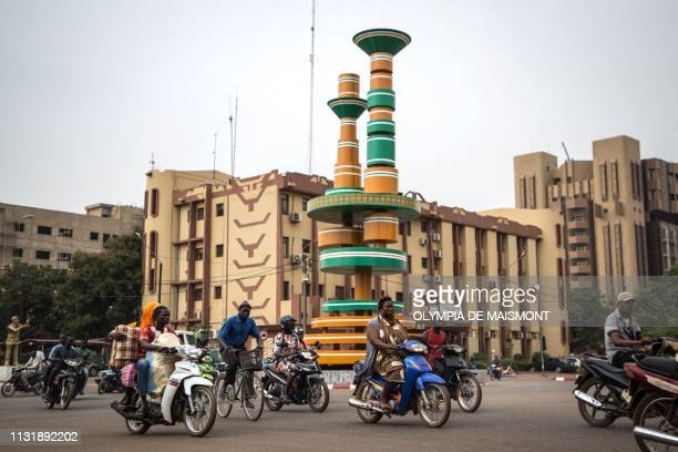 This picture taken on March 20, 2019 shows people riding bicycles and motorbikes around the filmmakers roundabout in Ouagadougou.