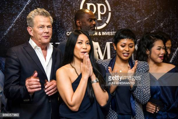 This picture taken on March 21 2018 shows Canadian composer and music producer David Foster posing with Indonesian singers Anggun C Sasmi Dira...