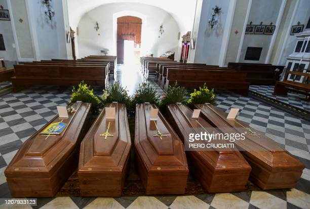 This picture taken on March 21, 2020 shows coffins on the ground of the church in Serina, near Bergamo, northern Italy. - Italy on March 21 reported...