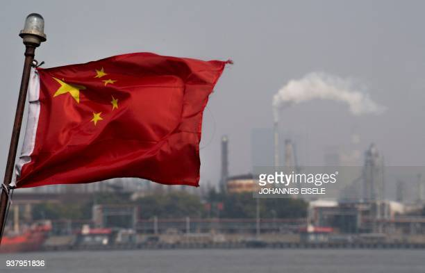 This picture taken on March 22 2018 shows a Chinese flag fluttering in front of the Shanghai Gaoqiao Company Refinery in Shanghai China launched...