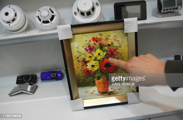 This picture taken on March 22, 2019 shows a painting installed with a hidden camera on display at a spy camera shop in the port city of Incheon. -...